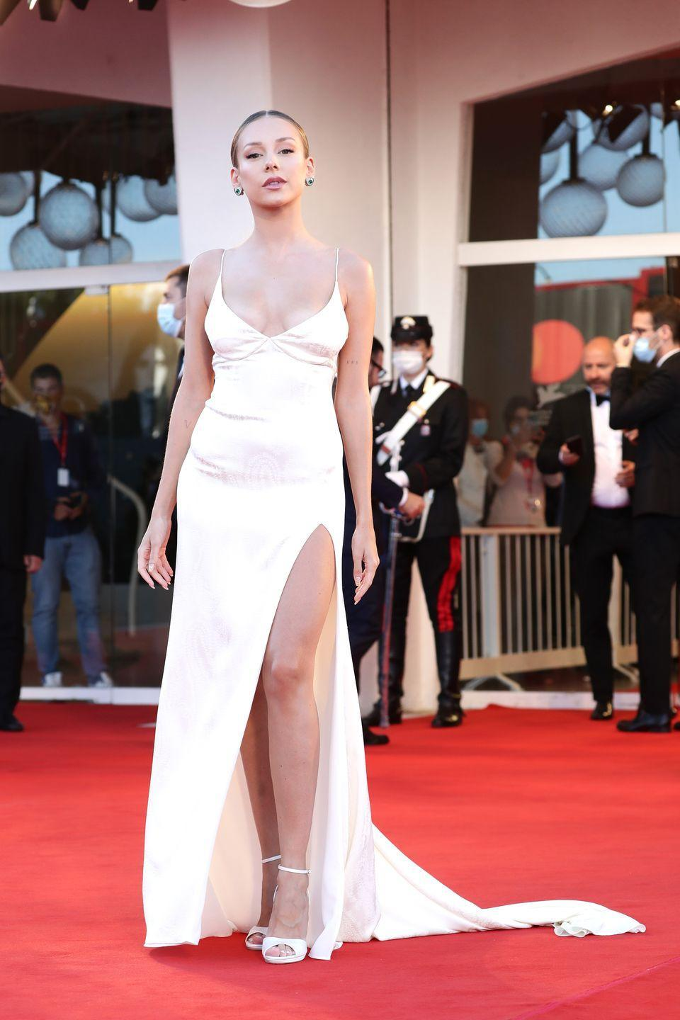 <p>Ester Expósito wears a white slipdress with a high slit.</p>
