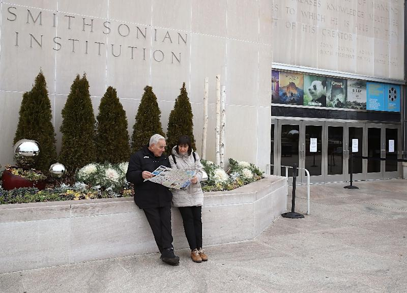 Tourists Enrico and Latisha Jacomini from Rome, Italy, look at a map after discovering the Smithsonian National Museum of American History is closed due to the partial shutdown of the US government (AFP Photo/MARK WILSON)