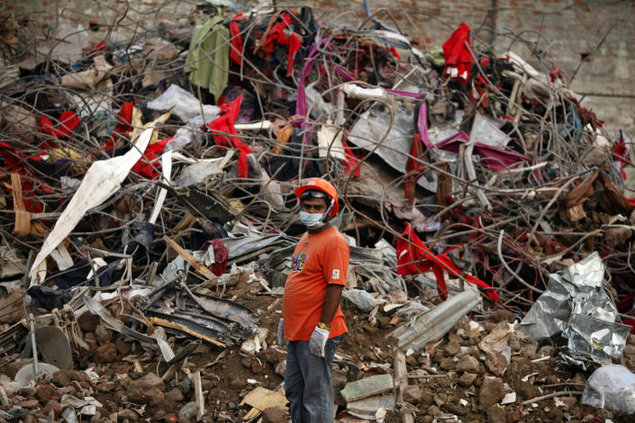 A Bangladeshi rescuer stands amid the rubble of a garment factory building that collapsed on April 24 as they continue searching for bodies in Savar, near Dhaka, Bangladesh, Sunday, May 12, 2013. Search teams resumed their rain-interrupted work Sunday as the death toll from the collapse continued to climb past 1,100. (AP Photo/A.M. Ahad)