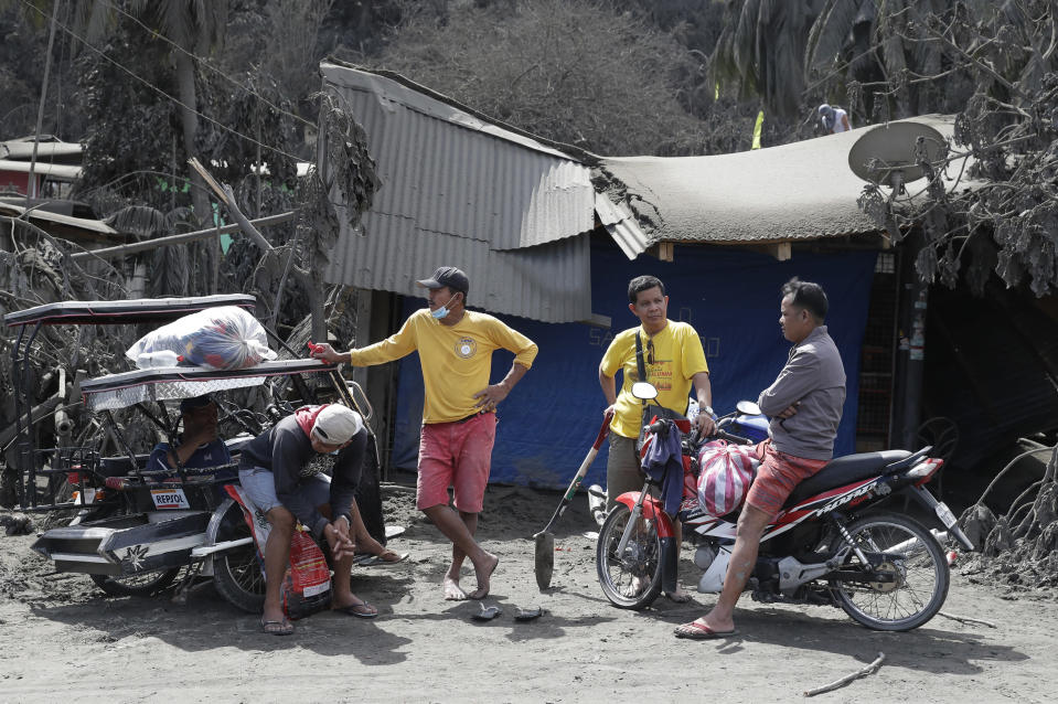 In this Jan. 14, 2020, photo, residents chat beside a damaged structure in Laurel, Batangas province, southern Philippines, as Taal volcano continues to spew ash. So far no one has been reported killed in the eruption, but the disaster is spotlighting the longstanding dilemma of how the government can move settlements away from danger zones threatened by volcanoes, landslides, floods and typhoons in one of the world's most disaster-prone countries. (AP Photo/Aaron Favila)