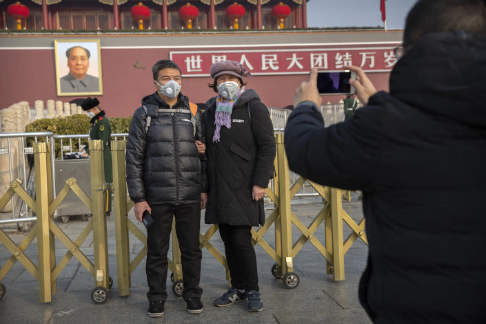 Tourists wear face masks as they pose for photos at Tiananmen Gate adjacent to Tiananmen Square in Beijing, Monday, Jan. 27, 2020. China on Monday expanded sweeping efforts to contain a viral disease by postponing the end of this week's Lunar New Year holiday to keep the public at home and avoid spreading infection as the death toll rose to 80. (AP Photo/Mark Schiefelbein)