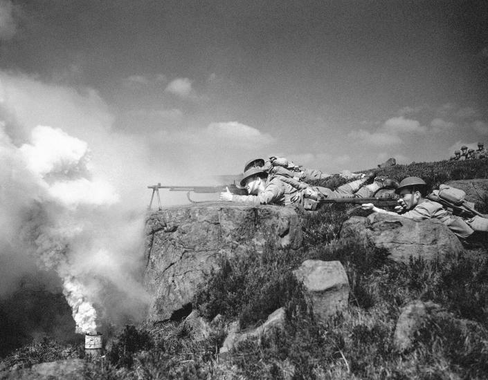 FILE - In this May 21, 1942 file photo, sniping from a rocky Irish hilltop, American troops man their Browning automatics and M-1 rifles through a haze of smoke screen during invasion maneuvers, in Ireland. Not since World War II, when people carried Ration Books, when buying cars, firewood and nylon was restricted, when men were drafted and women volunteered in the war effort, has the entire nation been asked to truly sacrifice for a greater good. (AP Photo, File)