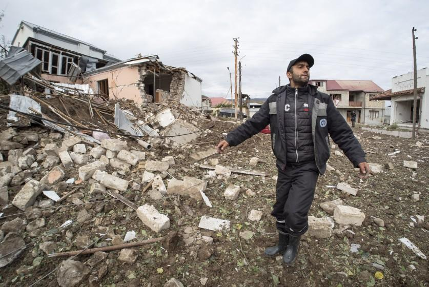 A man gestures near a house destroyed by shelling by Azerbaijan's artillery during a military conflict in Stepanakert, self-proclaimed Republic of Nagorno-Karabakh, Thursday, Oct. 8, 2020. Armenia accused Azerbaijan of firing missiles into the capital of the separatist territory of Nagorno-Karabakh, while Azerbaijan said several of its towns and its second-largest city were attacked. (AP Photo)