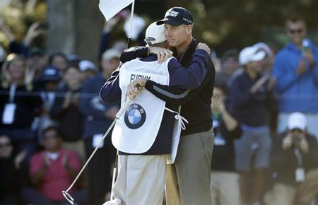 Furyk of the U.S. hugs his caddy after shooting a 59 during the second round of the BMW Championship golf tournament in Lake Forest
