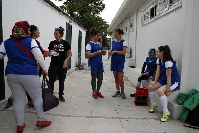 In this Wednesday, May 22, 2019 photo, members of Hestia FC Women's Refugee Soccer team talk outside the locker room before a train session in Athens. Many of the players at Hestia FC weren't allowed to play or even watch soccer matches in their home countries. Hestia FC was set up by the Olympic Truce Centre, a non-government organization created in 2000 by the International Olympic Committee and Greek Foreign Ministry. (AP Photo/Thanassis Stavrakis)