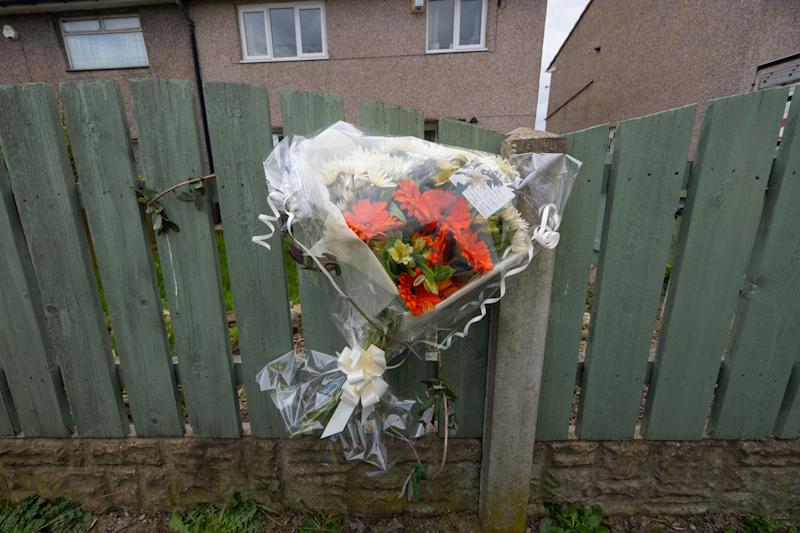 """Floral tributes left outside a house. Police and forensics at a house in Barnsley, March 30 2020. A man has been arrested on suspicion of murder after police were called to an address in Barnsley yesterday. See SWNS story SWLEmurder. A man has been arrested on suspicion of murder after a woman in her 30s was found stabbed to death at a house in a quiet village. South Yorkshire Police say officers were called to an address in Middlecliffe at 5pm yesterday (Sun) over """"concerns for someone's safety"""". When they arrived the victim, aged 31, was found with stab wounds. An air ambulance was spotted landing in a nearby field and paramedics rushed to the property but the injured woman was pronounced dead at the scene. A 40-year-old man has been arrested on suspicion of murder and remains in police custody this morning. The victim has been named locally as NHS worker and mum-of-three Victoria Charlotte Woodhall. A friend of her family confirmed Mrs Woodhall was working as an Operating Department Practitioner for the NHS."""