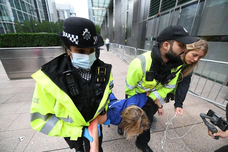 A Met Police officer and a Canary Wharf security guard carry a doctor away by her arms and legs after she refused to move herself (Gareth Morris)