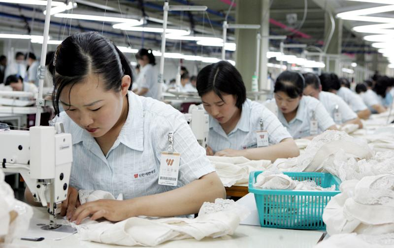 """FILE - In this June 22, 2006 file photo, North Koreans work at a factory of South Korean apparel maker Shinwon company in the inter-Korean industrial park in Kaesong, North Korea. South Korea on Thursday, April 25, 2013 warned of an unspecified """"grave measure"""" if North Korea rejects talks on the jointly run factory park shuttered for nearly a month - setting up the possible end of the last remaining major symbol of inter-Korean cooperation.(AP Photo/Ahn Young-joon, File)"""