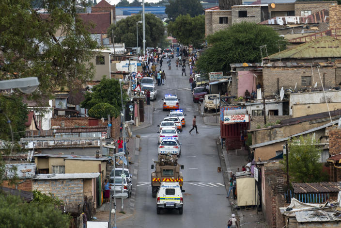 South African National Defense Forces and Police patrol the densely populated Alexandra township east of Johannesburg Friday, March 27, 2020. South Africa went into a nationwide lockdown for 21 days in an effort to mitigate the spread to the coronavirus, but in Alexandra, many people were gathering in the streets disregarding the lockdown. The new coronavirus causes mild or moderate symptoms for most people, but for some, especially older adults and people with existing health problems, it can cause more severe illness or death.(AP Photo/Jerome Delay)