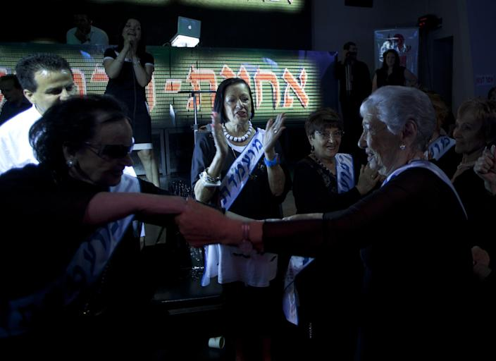 """Holocaust survivors dance as they participate in a beauty pageant, in the northern Israeli city of Haifa, Thursday, June 28, 2012. Fourteen women who lived through the horrors of World War II paraded on stage Thursday night in an unusual pageant, vying for the honor of being Israel's first """"Miss Holocaust Survivor."""" (AP Photo/Sebastian Scheiner)"""