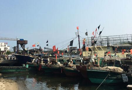 Fishing boats with Chinese national flags are seen at a harbour in Tanmen, Hainan province, April 5, 2016. REUTERS/Megha Rajagopalan