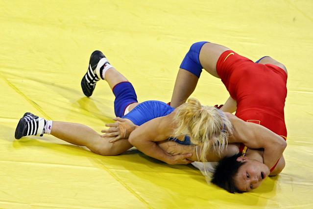 BEIJING - AUGUST 16: Li Xiaomei of China (red) competes against Irini Merleni of Ukraine in the women's 48kg freestyle wrestling event held at the China Agriculture University Gymnasium on Day 8 of the Beijing 2008 Olympic Games on August 16, 2008 in Beijing, China. (Photo by Jeff Gross/Getty Images)