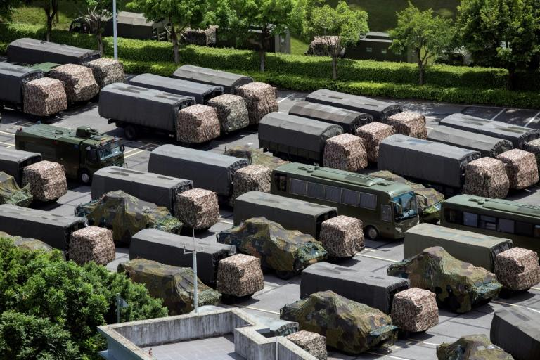 Trucks and armoured personnel carriers from China's security forces are parked at a stadium in Shenzhen, Guangdong province, on the border with Hong Kong