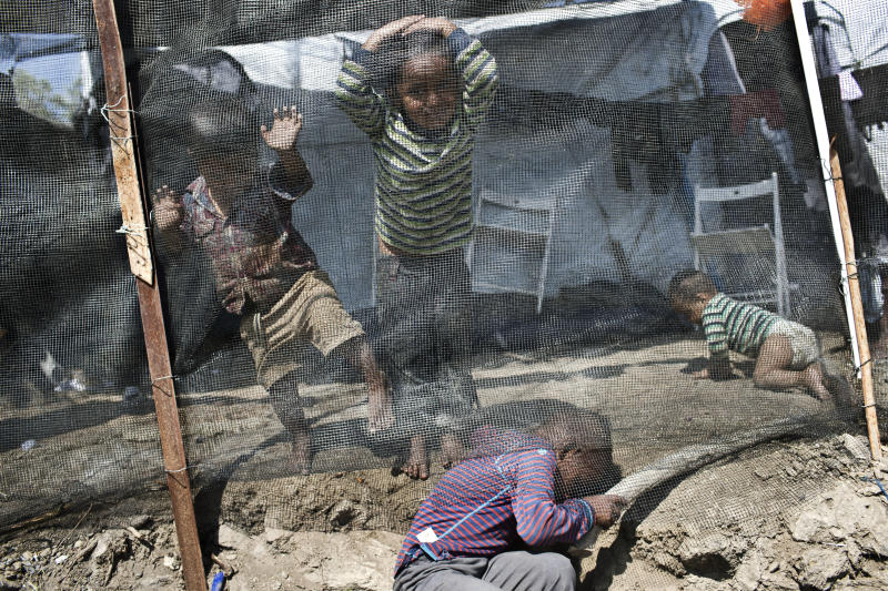 FILE - In this Wednesday May 2, 2018 file photo, children play at a makeshift refugee camp outside Moria on the northeastern Aegean island of Lesbos, Greece. European governments breathed a sigh of relief as the European Union reached a deal with Turkey designed to stop hundreds of thousands of refugees and migrants heading into the heart of Europe. For many of those who had fled war, hunger and poverty hoping for a bright future on the continent, the deal shattered their dreams. (AP Photo/Petros Giannakouris, File)