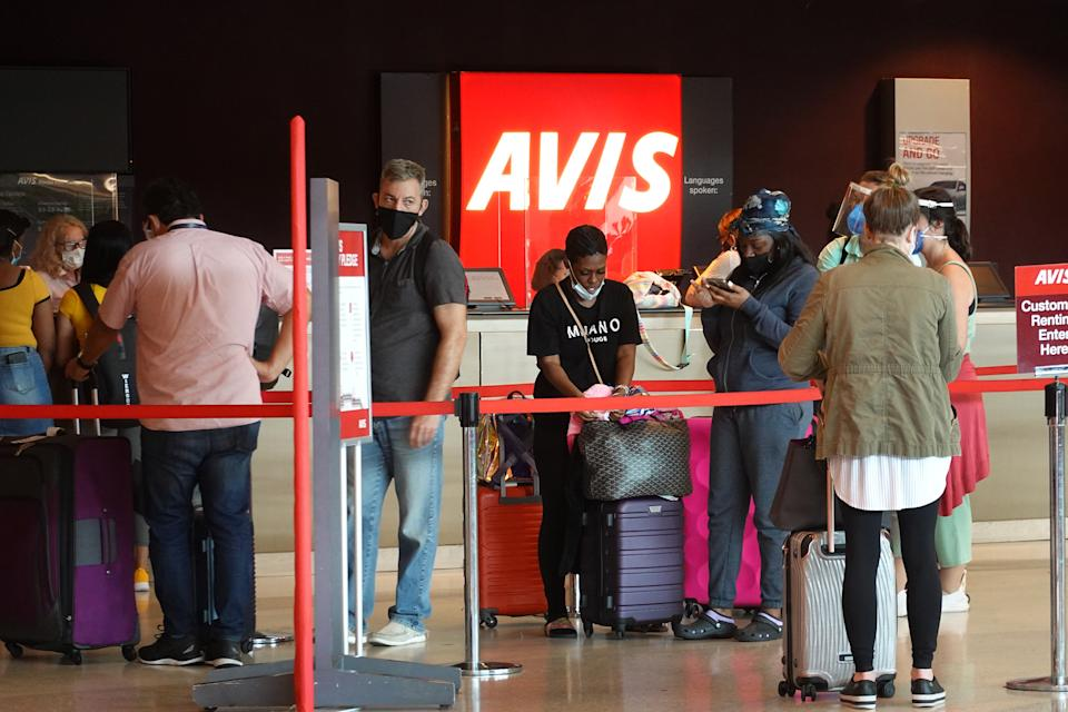 MIAMI, FLORIDA - APRIL 12: People wait in line at Avis rental agency in the Miami International Airport Car Rental Center on April 12, 2021 in Miami, Florida. Customers are finding that car rental agencies have limited or no supply of vehicles as people begin traveling again after being locked down during the pandemic. (Photo by Joe Raedle/Getty Images)