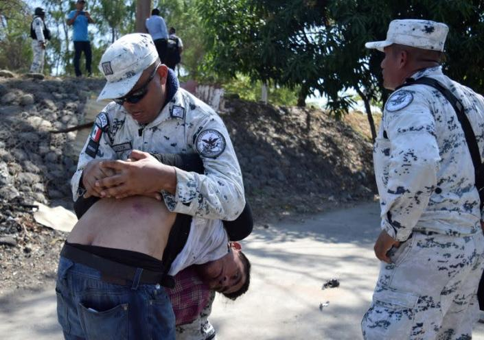 A member of Mexico's National Guard detains a migrant, part of a caravan travelling to the U.S., near the border between Guatemala and Mexico, in Ciudad Hidalgo
