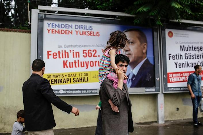 A Syrian refugee carries a girl on his shoulders in front of a billboard featuring a portrait of Turkish President Recep Tayyip Erdogan in Istanbul, on May 27, 2015 (AFP Photo/Yasin Akgul)
