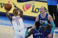Oklahoma City Thunder guard Theo Maledon (11) shoots in front of Charlotte Hornets guard Terry Rozier (3) and center Cody Zeller, right, in the first half of an NBA basketball game Wednesday, April 7, 2021, in Oklahoma City. (AP Photo/Sue Ogrocki)