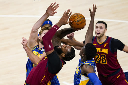 Cleveland Cavaliers center Andre Drummond (3)n shoots between Indiana Pacers forward Domantas Sabonis (11) and guard Victor Oladipo (4) during the second half of an NBA basketball game in Indianapolis, Thursday, Dec. 31, 2020. (AP Photo/Michael Conroy)