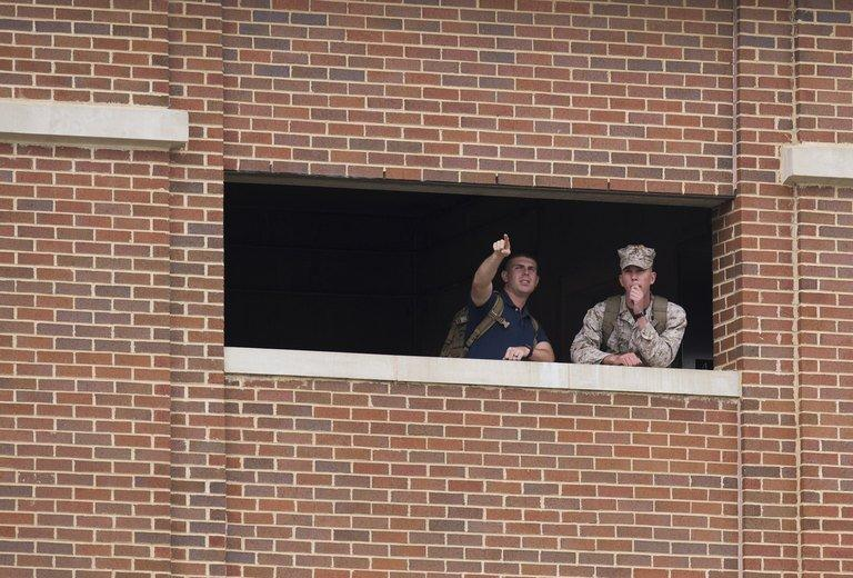 Members of the military look out from a nearby building toward police units responding to a shooting at the Navy Yard in Washington, DC, September 16, 2013