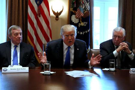 U.S. President Donald Trump, flanked by U.S. Senator Dick Durbin (D-IL) and Representative Steny Hoyer (D-MD), holds a bipartisan meeting with legislators on immigration reform at the White House in Washington, U.S. January 9, 2018.  REUTERS/Jonathan Ernst