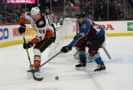 Anaheim Ducks left wing Max Jones (49) backhands the puck as Colorado Avalanche defenseman Mark Barberio (44) pokes at it during the second period of an NHL hockey game Wednesday, March 4, 2020 in Denver. (AP Photo/John Leyba)