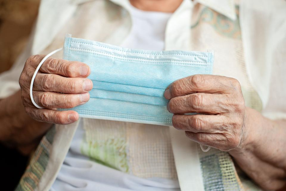 Old woman holds medical mask in hands, blank table (Photo: Getty Images)