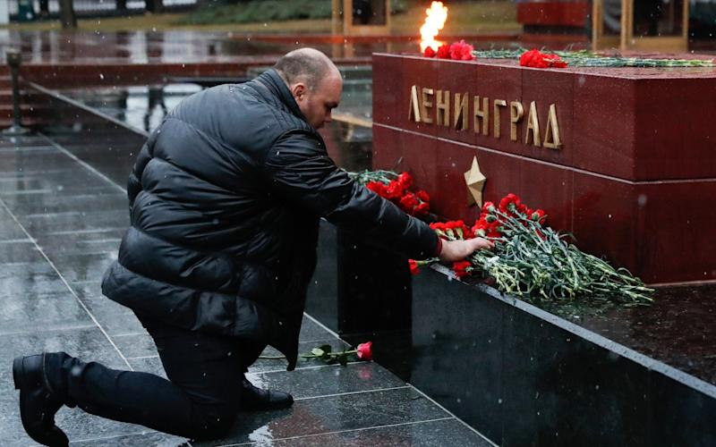 A man laying flowers at the Leningrad Hero City memorial by the Kremlin Wall in memory of the St Petersburg Metro explosion victims - Credit: TASS/Barcroft Images