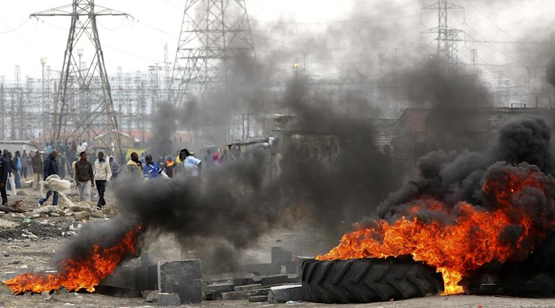 Miners burning tires as they barricade the streets in Lonmin Platinum Mine near Rustenburg, South Africa, Saturday, Sept. 8, 2012. As various stakeholders continued negotiations South African Justice Minister Jeff Radebe warned that the Government would clamp down on daily illegal marches by miners brandishing machetes, spears and clubs that have marked the strike. (AP Photo/Themba Hadebe)