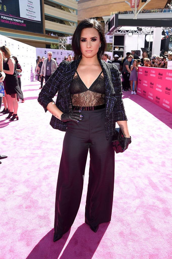 <p>This lacy look is not your typical pantsuit. Lovato, who is set to perform tonight, took her suit to the next level with her signature smoky eye and edgy leather fingerless gloves. <i>(Photo: Frazer Harrison/Getty Images)</i></p>