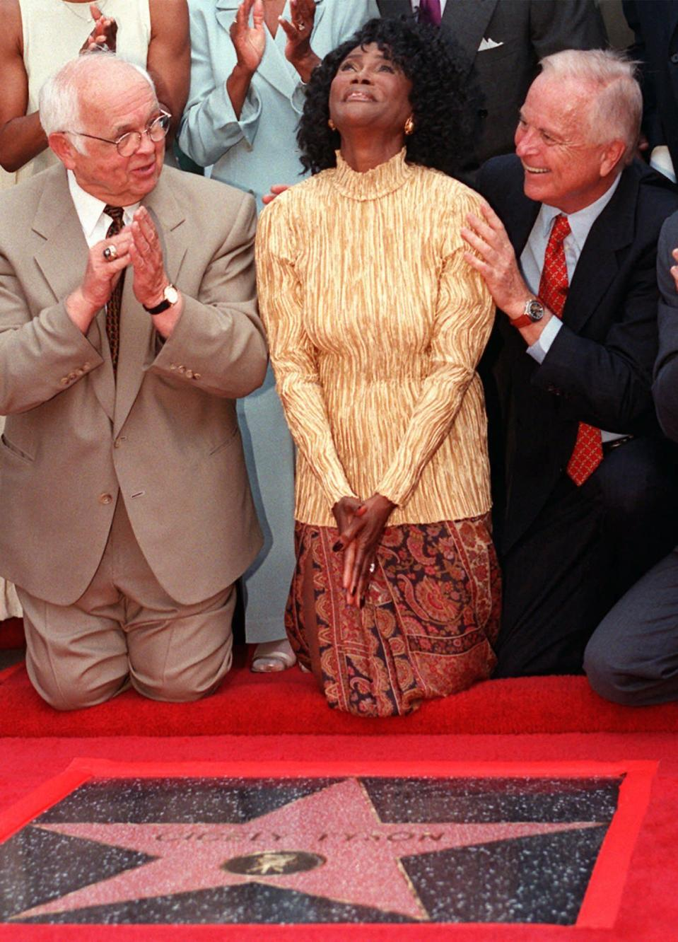 "FILE - Academy Award-nominated actress Cicely Tyson reacts to the unveiling of her star on the Hollywood Walk of Fame in the Hollywood section of Los Angeles, Thursday, Aug. 21, 1997. Honorary Mayor of Hollywood and chairman of the Walk of Fame committee Johnny Grant, left, and Los Angeles Mayor Richard Riordan joined Tyson for the unveiling. Tyson, the pioneering Black actress who gained an Oscar nomination for her role as the sharecropper's wife in ""Sounder,"" a Tony Award in 2013 at age 88 and touched TV viewers' hearts in ""The Autobiography of Miss Jane Pittman,"" has died. She was 96. Tyson's death was announced by her family, via her manager Larry Thompson, who did not immediately provide additional details. (AP Photo/Damian Dovarganes, File)"