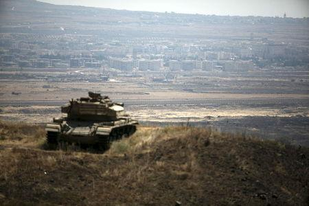 The Syrian area of Quneitra is seen in the background as an out-of-commission Israeli tank parks on a hill, near the ceasefire line between Israel and Syria, in the Israeli-occupied Golan Heights, August 21, 2015. Israel said it killed four Palestinian militants in an air strike on the Syrian Golan Heights on Friday, after cross-border rocket fire from Syria prompted the heaviest Israeli bombardment since the start of Syria's four-year-old civil war. REUTERS/Baz Ratner