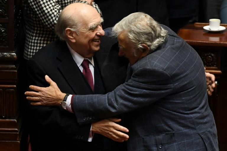 Uruguayan former presidents Julio Sanguinetti (left) and Jose Mujica, embrace during their last session as senators at the Congress in Montevideo on October 20, 2020