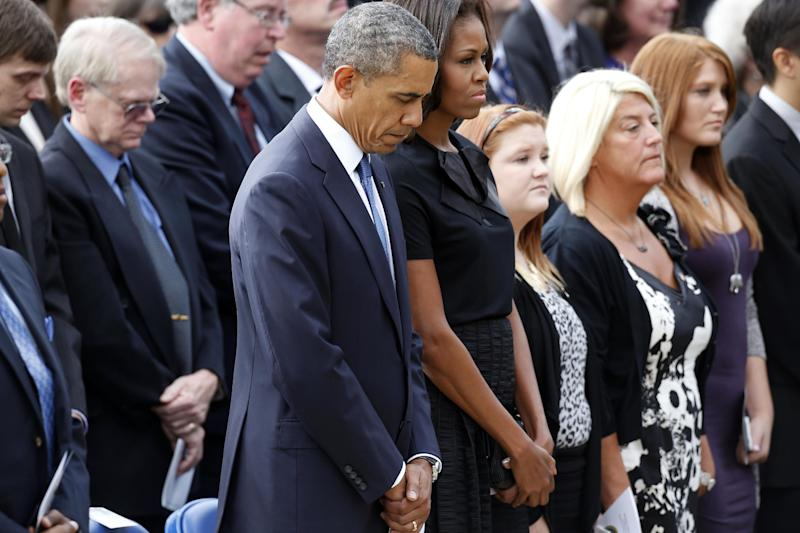 President Barack Obama and first lady Michelle Obama stand at a memorial service for the victims of the Washington Navy Yard shooting at Marine Barracks Washington Sunday, Sept. 22, 2013. A gunman killed 12 people in the Navy Yard on Monday, Sept. 16, 2013, before being fatally shot in a gun battle with law enforcement. The president and first lady Michelle Obama also visited with the victims' families. (AP Photo/Charles Dharapak)