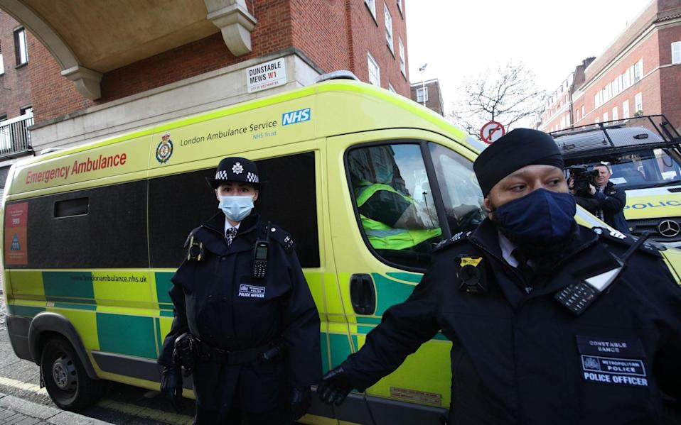 Police officers and security guards clear a pathway for an ambulance as it leaves the rear of the King Edward VII Hospital - PA
