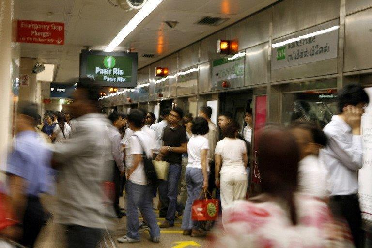 People get on and off a subway train at an MRT metro station in Singapore, February 15, 2007