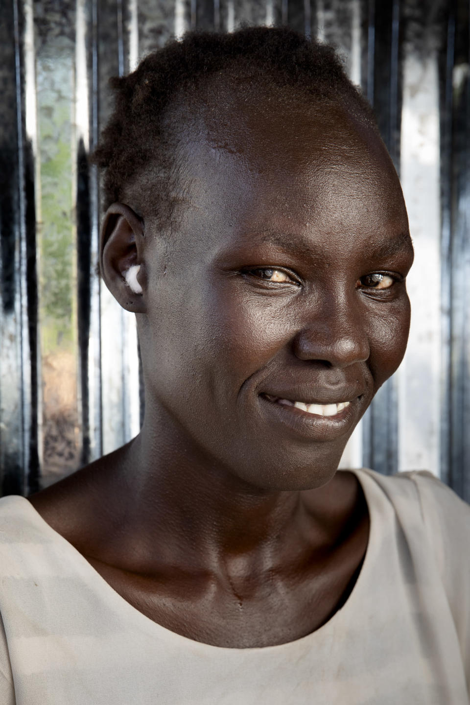 Belinda Idjidio, 36-years-old mother of 5, poses for a portrait at Paska Itwari Beda's Juba, South Sudan home, Saturday, May 29, 2021. With resources scarce, Beda and nine women formed a group that meets and contributes two of the barest necessities for warding off hunger and illness - money and bars of soap. They gather on Fridays, pooling supplies and handing them out to a different family every week. Over coffee, they share advice. (AP Photo/Adrienne Surprenant)