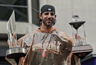 San Francisco Giants baseball player and World Series MVP Madison Bumgarner holds the MVP trophies during the victory parade for the 2014 World Series baseball champions on Friday, Oct. 31, 2014, in San Francisco. (AP Photo/Marcio Jose Sanchez)