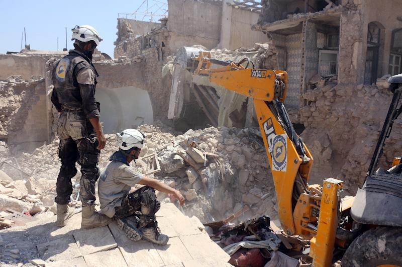 Syrian civil defence volunteers, known as the White Helmets, dig through the debris following an airstrike earlier in the day on August 20, 2016, the Jallum neighbourhood in the northern Syrian city of Aleppo