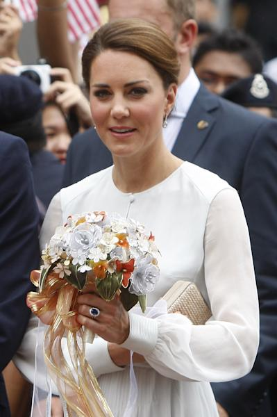 Britain's Kate, the Duchess of Cambridge, holds a bouquet of flowers while watching a cultural performance at KLCC park in Kuala Lumpur, Malaysia, Friday, Sept. 14, 2012. (AP Photo/Lai Seng Sin)