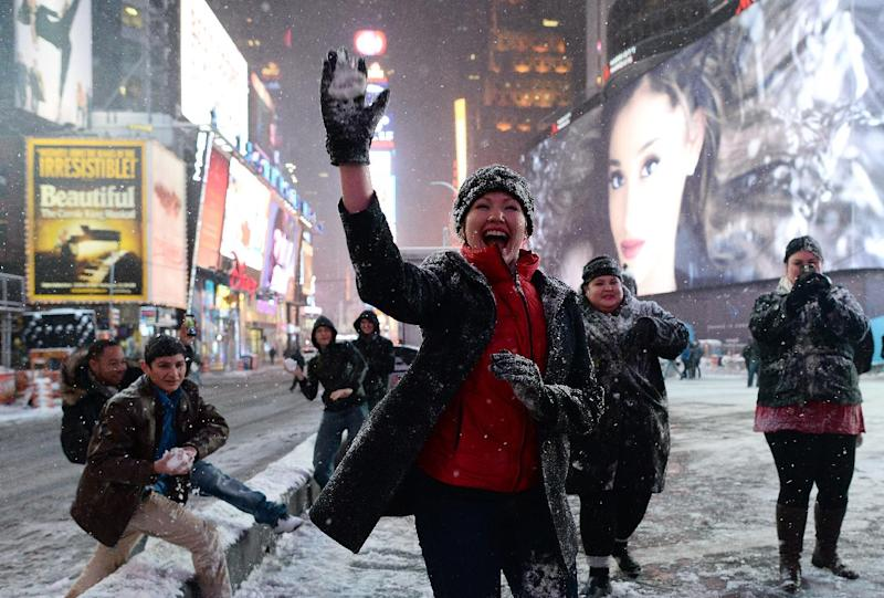 A group of young people from Texas have a snow-ball fight on a deserted street in New York's Times Square on January 26, 2015 (AFP Photo/Jewel Samad)