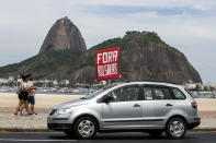 """People hold a sign that reads """"Bolsonaro out,"""" during a protest against the government's response in combating COVID-19 and demanding the impeachment of Brazilian President Jair Bolsonaro, backdropped by the Sugar Loaf mountain in Rio de Janeiro, Brazil, Sunday, Jan. 31, 2021. (AP Photo/Bruna Prado)"""