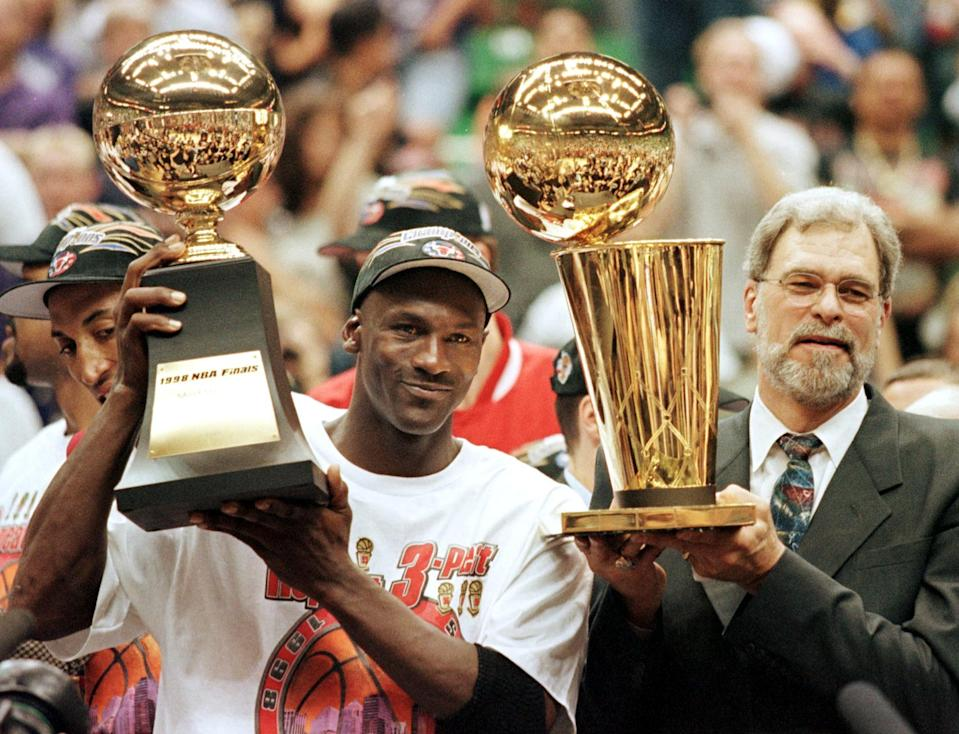 Michael Jordan (L) and Chicago Bulls head coach Phil Jackson (R) Most Valuable Player trophy (L) and the Larry O'Brian trophy (R) 14 June after winning game six of the NBA Finals. (Photo by JEFF HAYNES / AFP) (Photo by JEFF HAYNES/AFP via Getty Images)