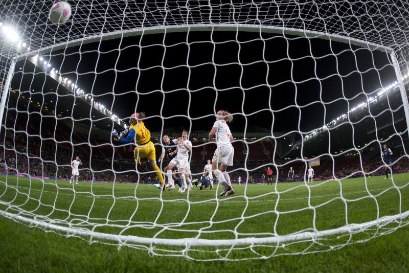Canada's goalkeeper Erin Mcleod, center left, dives in vain as the United States' Alex Morgan, bottom center, scores the winning goal during their semifinal women's soccer match at the 2012 London Summer Olympics, Monday, Aug. 6, 2012, at Old Trafford Stadium in Manchester, England. (AP Photo/Jon Super)