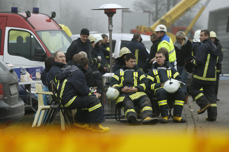 Rescue workers take a break, in front of the Maxima supermarket in Riga, Latvia, Saturday, Nov. 23, 2013. Scores of people have died, including three firefighters, after an enormous section of roof collapsed at a Latvian supermarket in the country's capital, emergency medical officials said Friday. The roof fell Thursday evening in the Latvian capital of Riga as customers were doing after-work shopping. Preliminary reports indicate the roof caved in due to either faulty construction or building activities on the roof, where workers were creating a garden area and children's playground for a new high-rise residential building adjacent to the supermarket. (AP Photo/Mindaugas Kulbis)