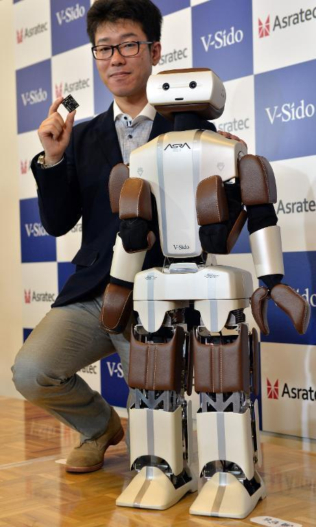 """Wataru Yoshizaki (L), robot engineer for Asratec, poses with humanoid robot """"Asra C1"""" on June 11, 2014, Shinzo Abe expects such technology to boost the economy"""