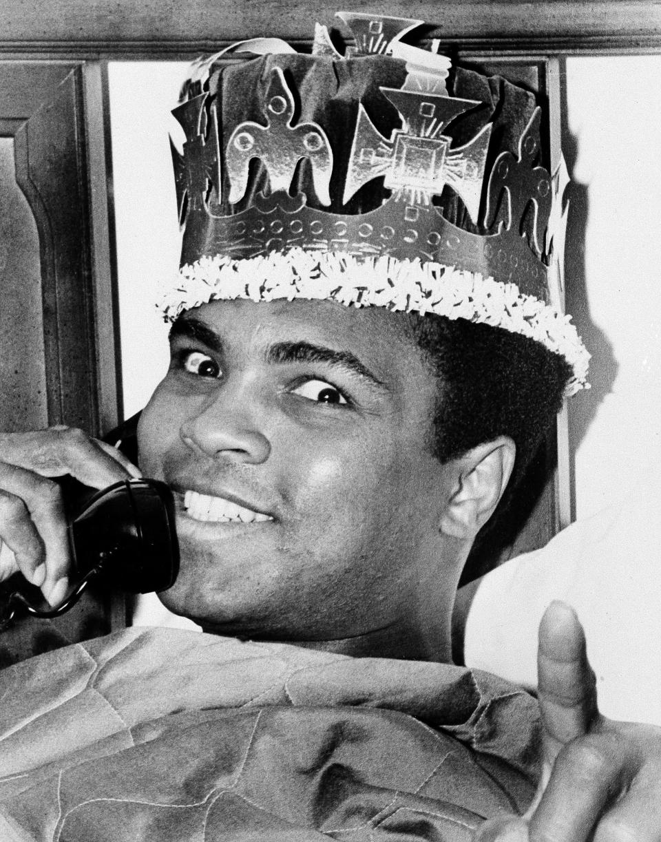 FILE - Muhammad Ali wears a crown while speaking on the phone in Miami Beach, Fla., ahead of his March 8 fight against Joe Frazier in New York, in this March 6, 1971, file photo. Their first fight at Madison Square Garden was so epic it was billed as the Fight of the Century, and 50 years later it reigns undefeated. (AP Photo/Joe Migon, File)