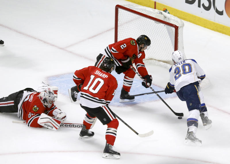 Chicago Blackhawks defenseman Duncan Keith (2) keeps St. Louis Blues left wing Alexander Steen (20) from getting a shot on goal as goalie Corey Crawford (50) and Patrick Sharp watch during the first period in Game 3 of a first-round NHL hockey Stanley Cup playoff series game Monday, April 21, 2014, in Chicago. (AP Photo/Charles Rex Arbogast)