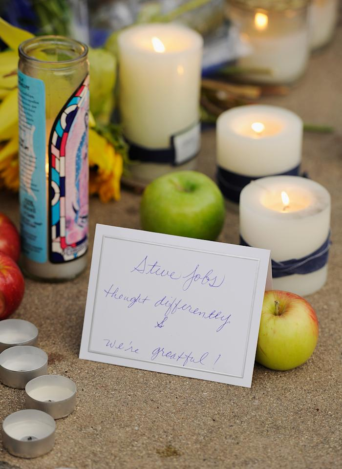 CUPERTINO, CA - OCTOBER 06:  Cards, apples and candles sit at a makeshift memorial for Steve Jobs at the Apple headquarters on October 5, 2011 in Cupertino, California. Jobs, 56, died October 5, 2011.Jobs co-founded Apple in 1976 and is credited with marketing the world's first personal computer in addition to the popular iPod, iPhone and iPad.  (Photo by Kevork Djansezian/Getty Images)