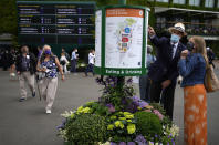 People walk around the grounds of the Wimbledon Tennis Championships in London, Tuesday June 29, 2021. (AP Photo/Alastair Grant)
